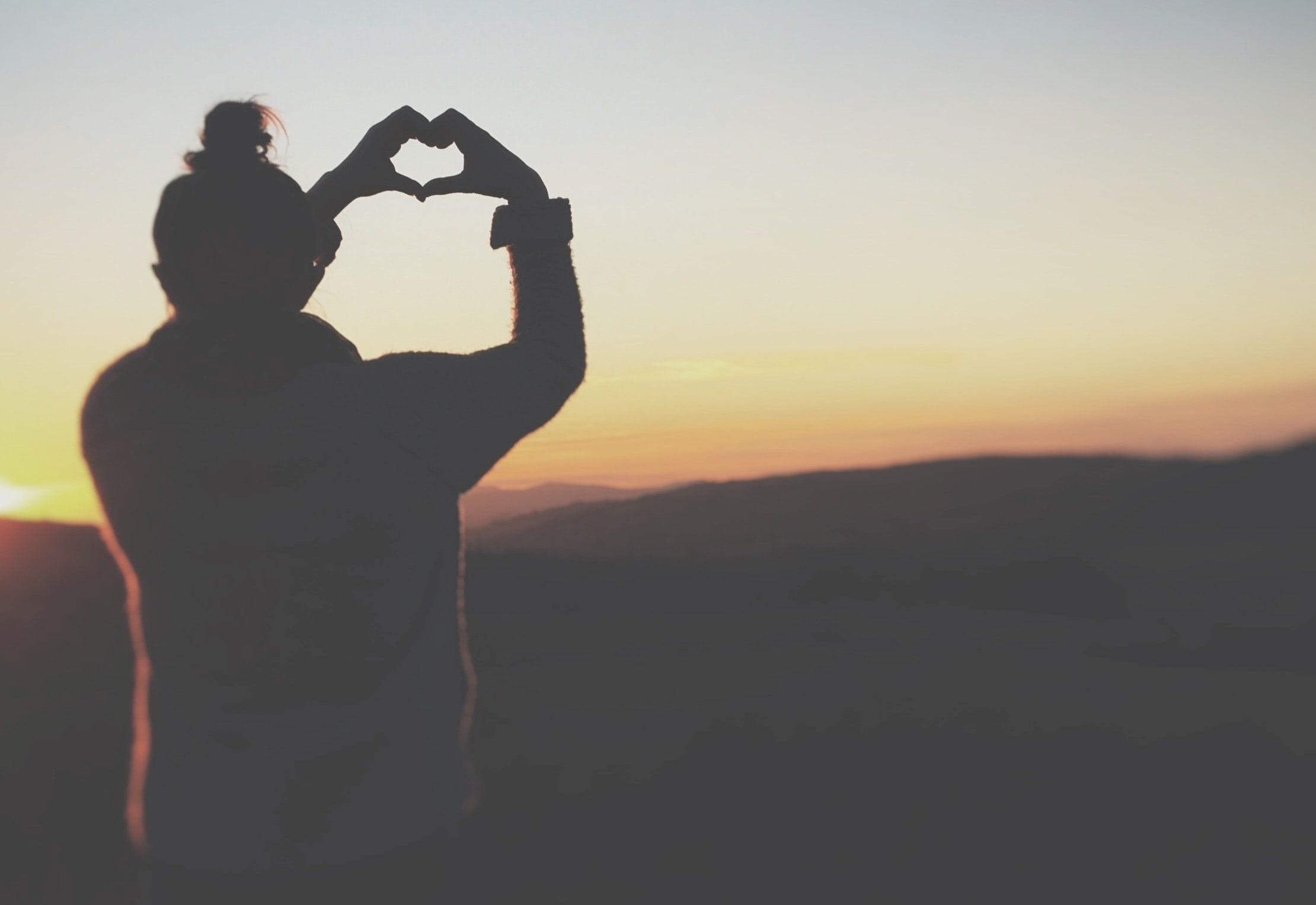 A person looking over the horizon, making a heart with their hands