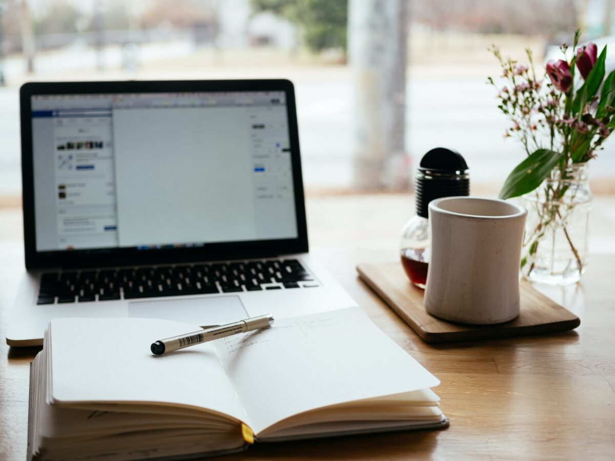 A laptop sitting on a desk with an open notebook in front of it and a mug beside it, demonstrating content marketing