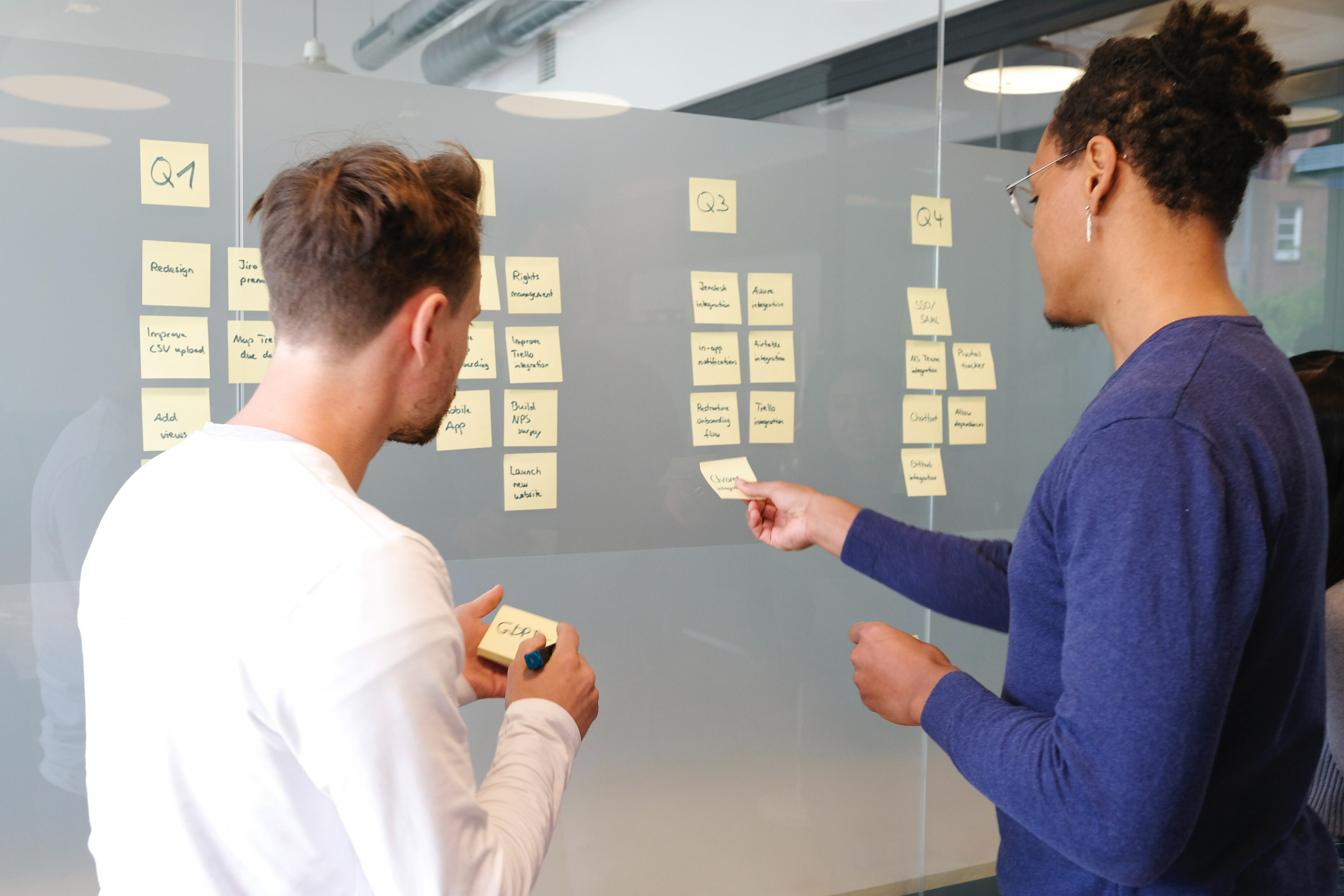 Two people putting sticky notes on a wall as a way of planning