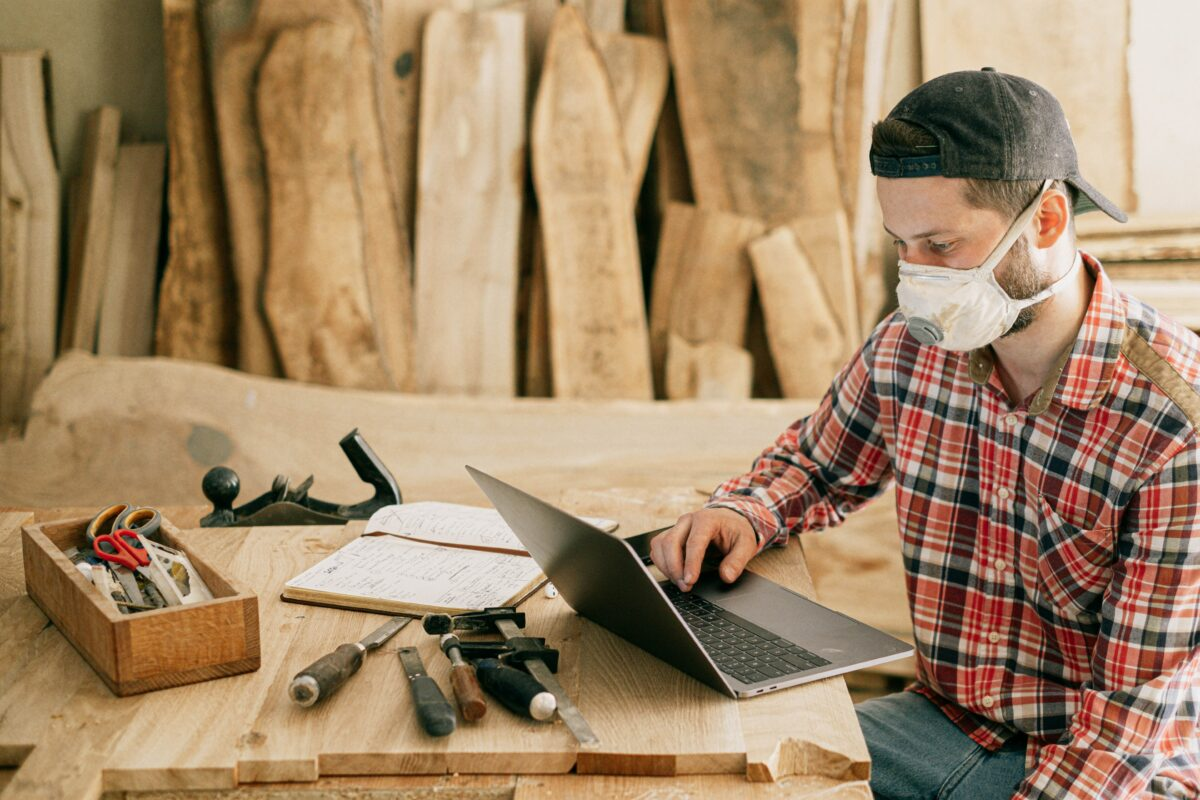 A person sitting in a workshop using a laptop, working in the construction industry