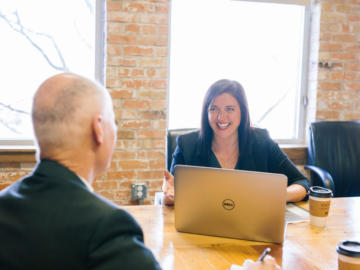 A woman sitting in front of a laptop and speaking to a colleague, showing pain points business coaches experience