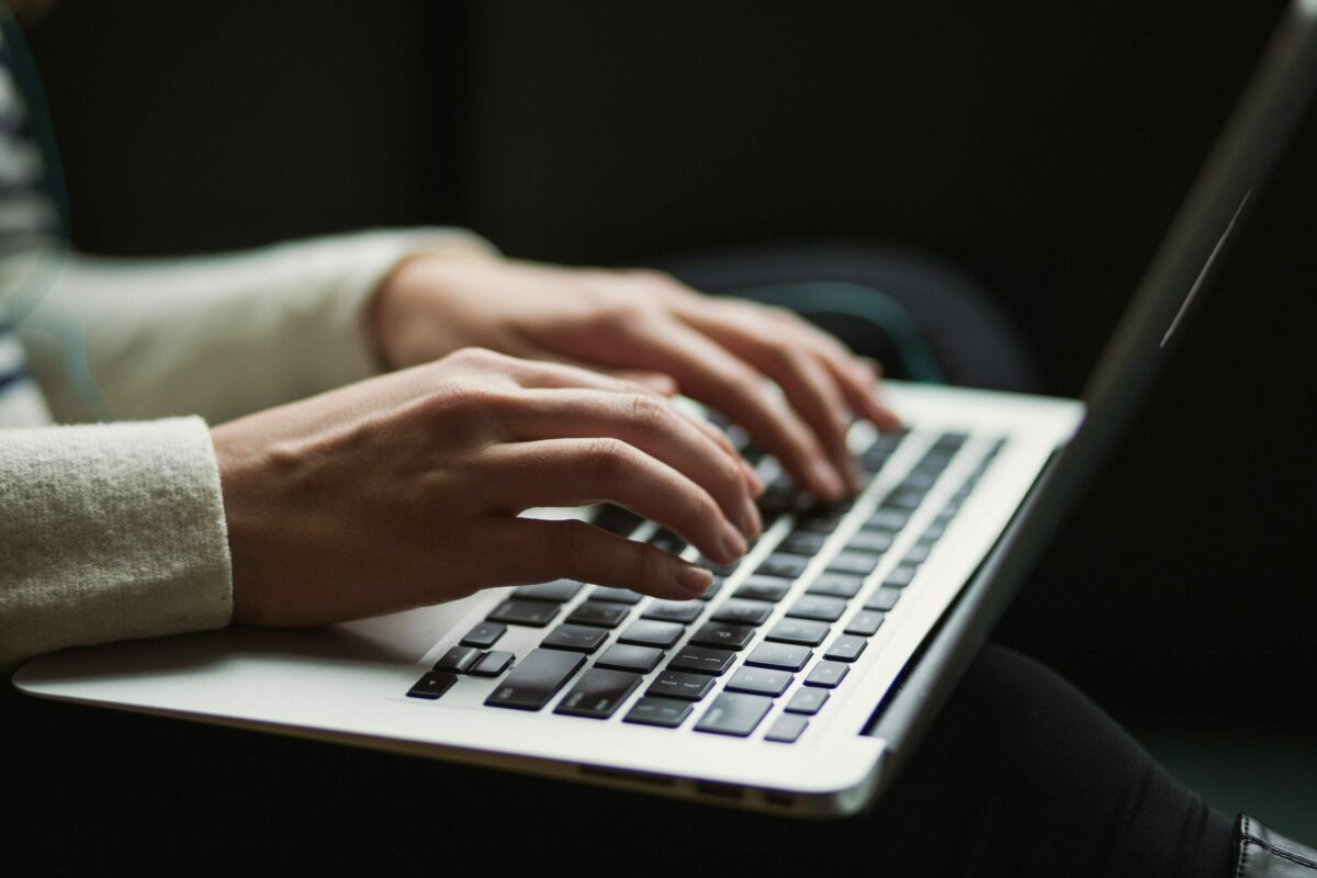 A hands-only view of someone typing on a laptop to represent the importance of evergreen content
