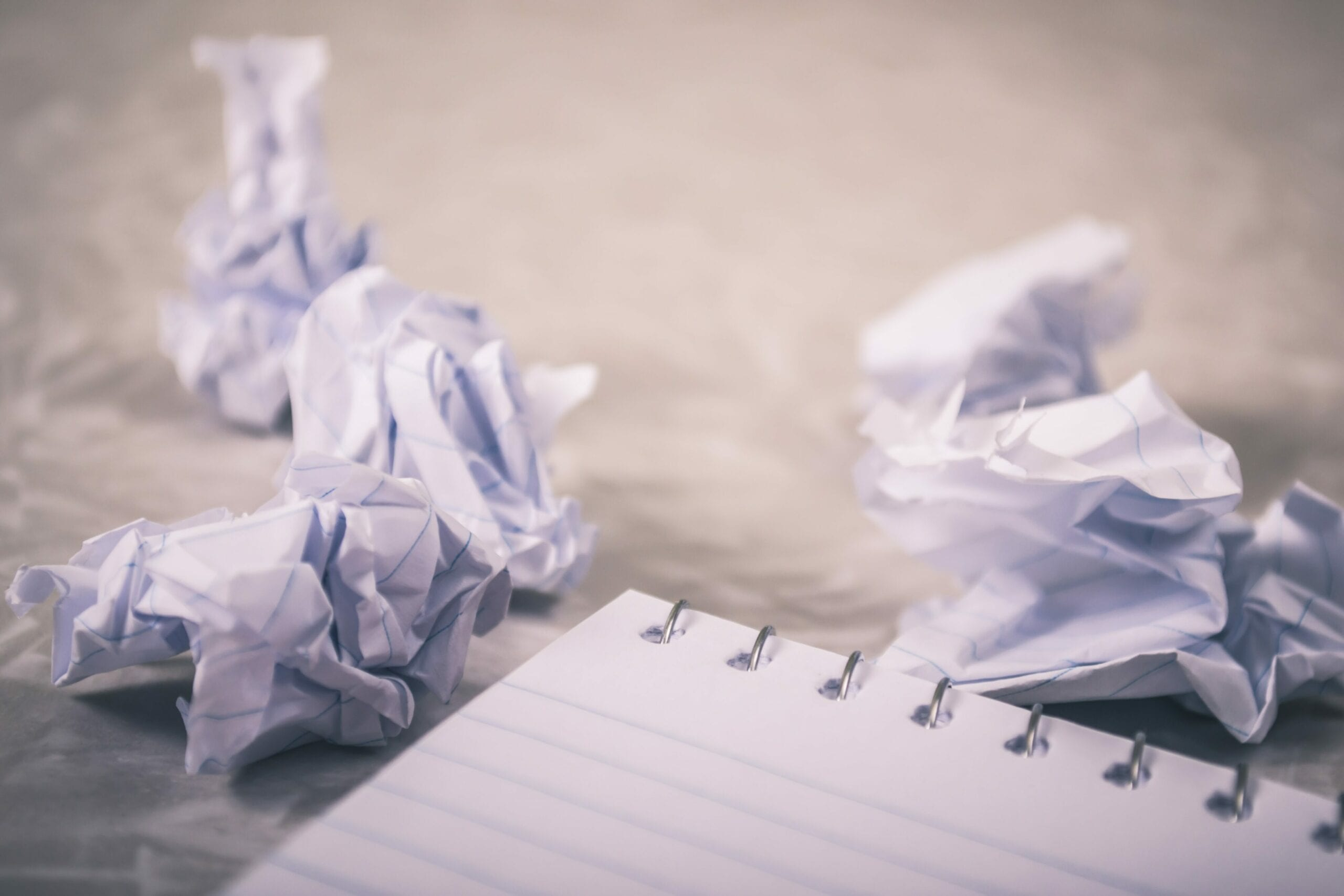 A few crumpled up pieces of paper next to an empty notebook