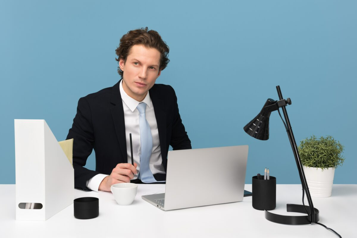 A man in a suit sitting at a desk in front of a laptop, demonstrating the importance of blog content