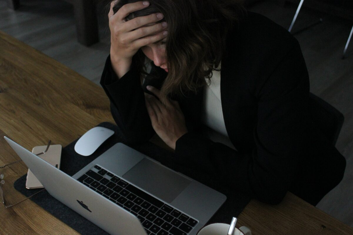 A person sitting at a laptop with their head in their hand, clearly stressed. This is to show your friends and family should not make your website