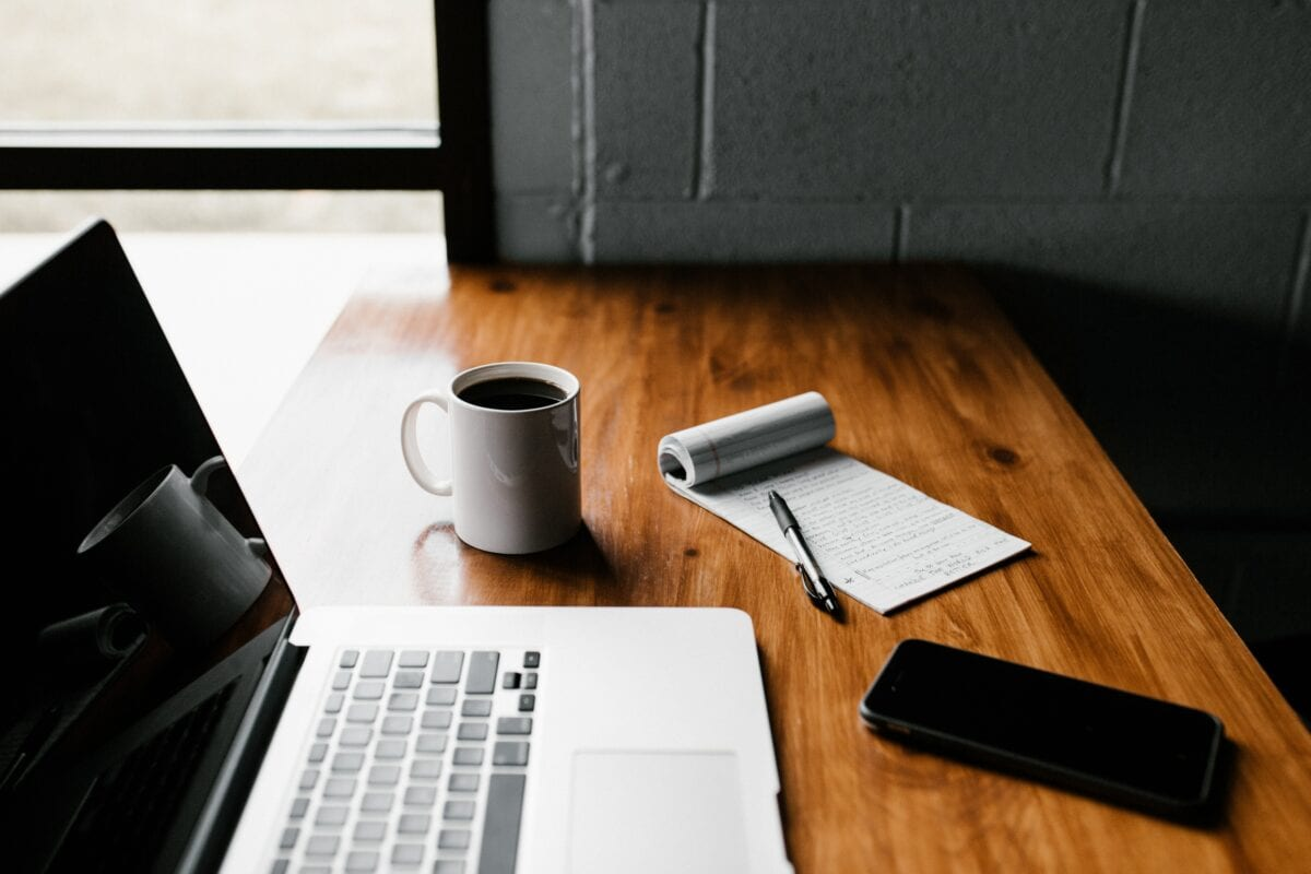 A laptop and notepad are sitting on a table next to a coffee mug.