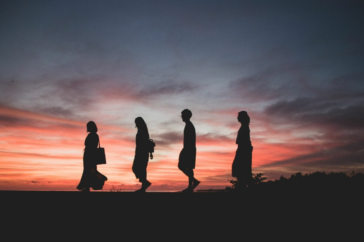 Four people walking in front of a sunset