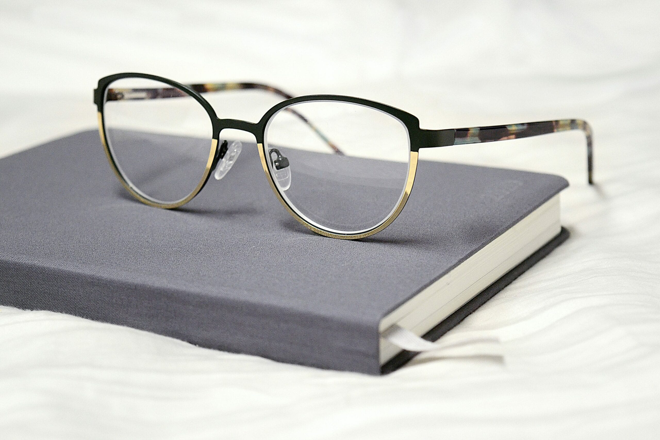A pair of glasses sitting on a jounal