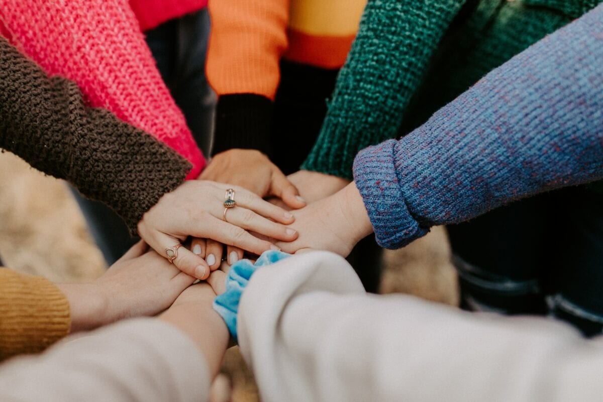 People standing together putting their hands in the middle