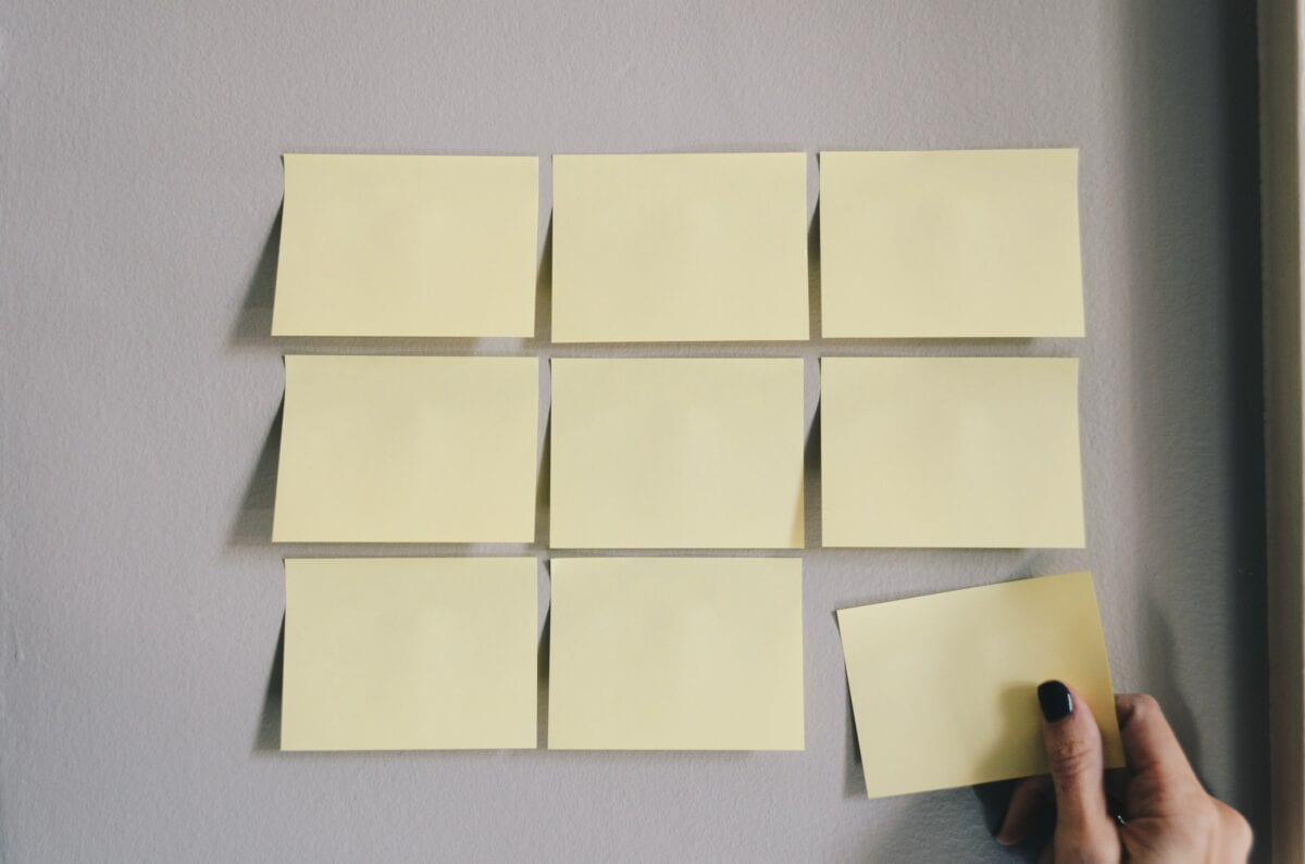 Someone putting sticky notes on a wall