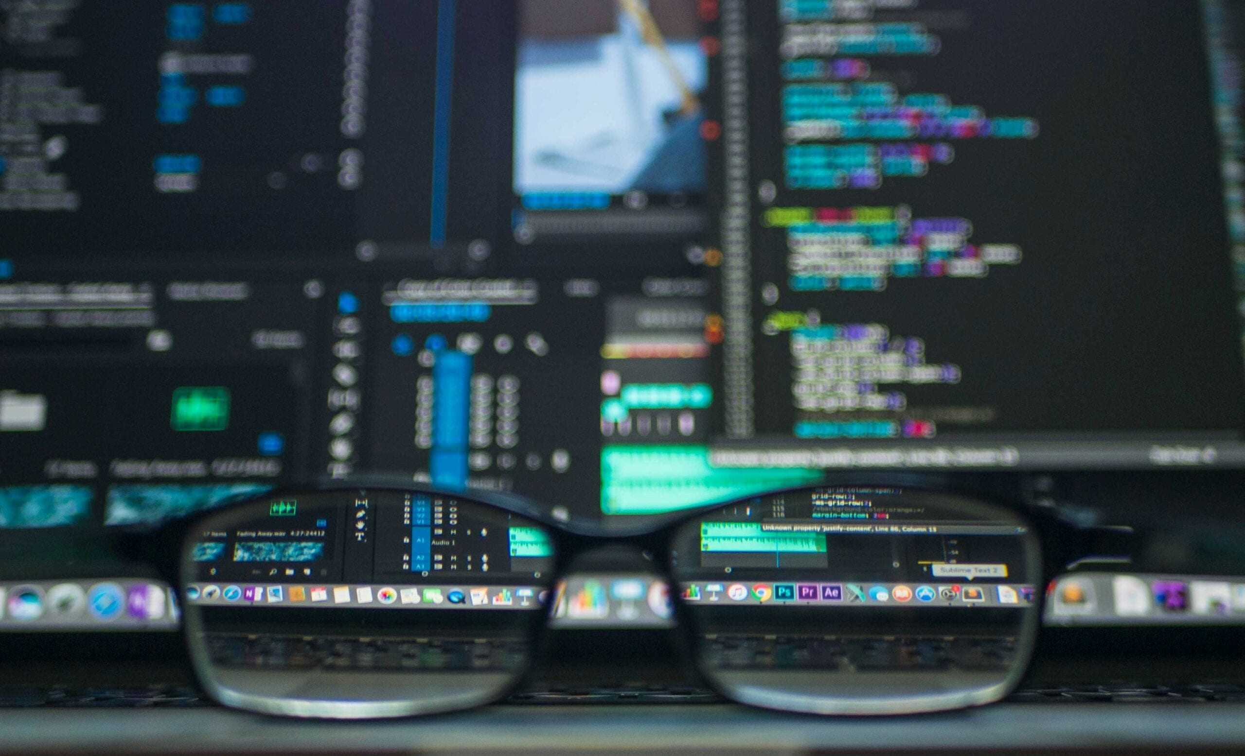 Glasses sitting in front of a screen. The screen has coding on it