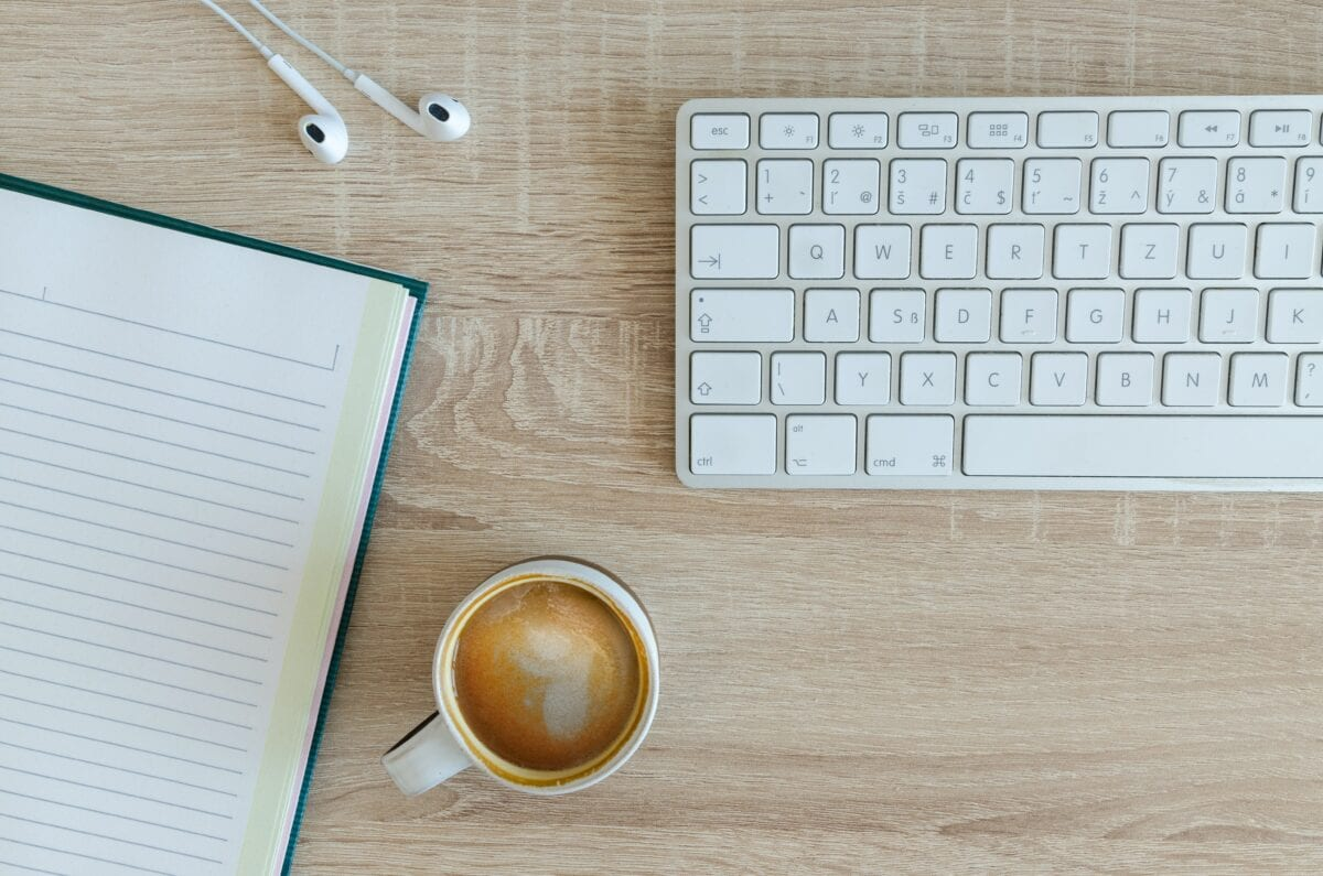A cup of coffee sitting next to a keyboard, notebook, and earbuds.