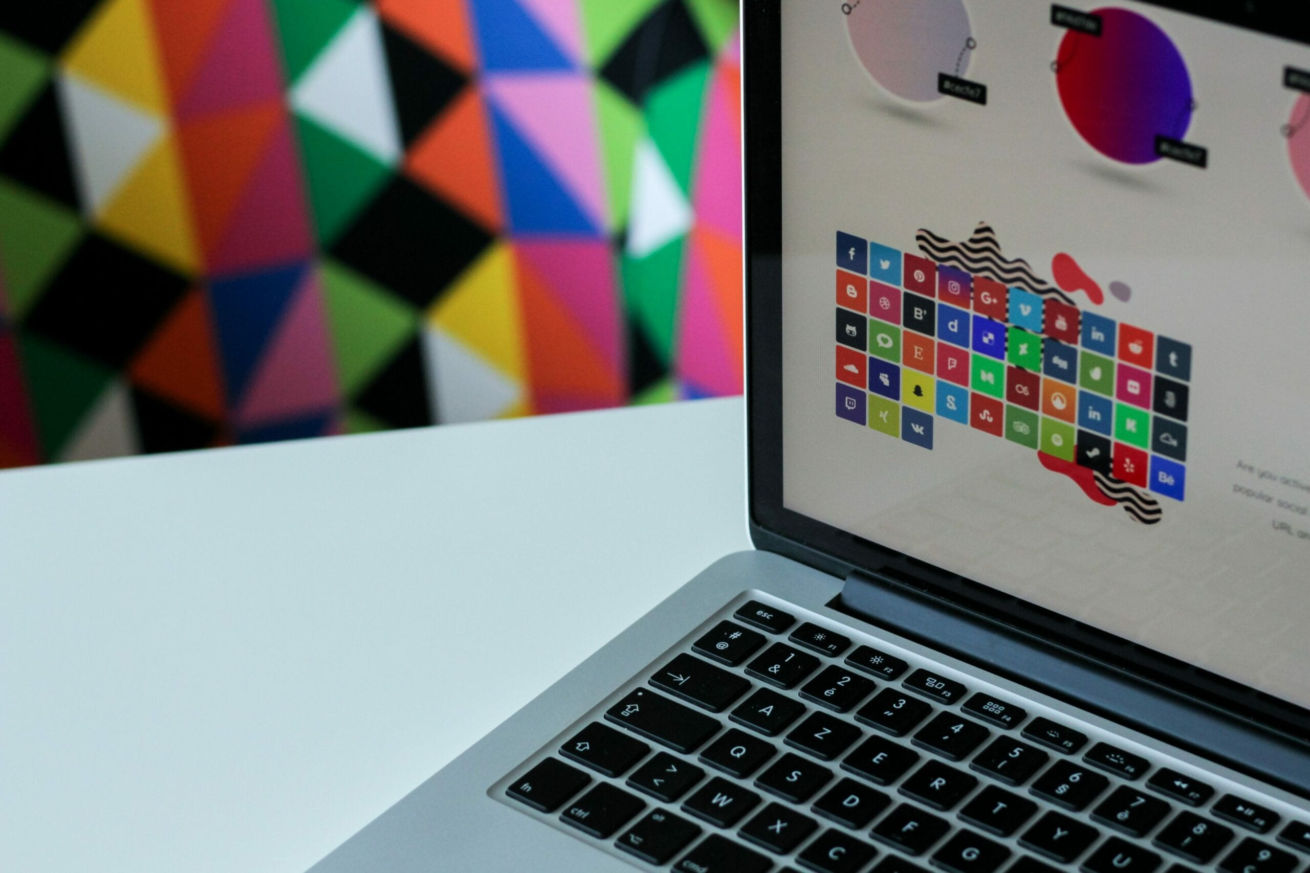 A laptop with a brightly-colored design on the screen and in the background