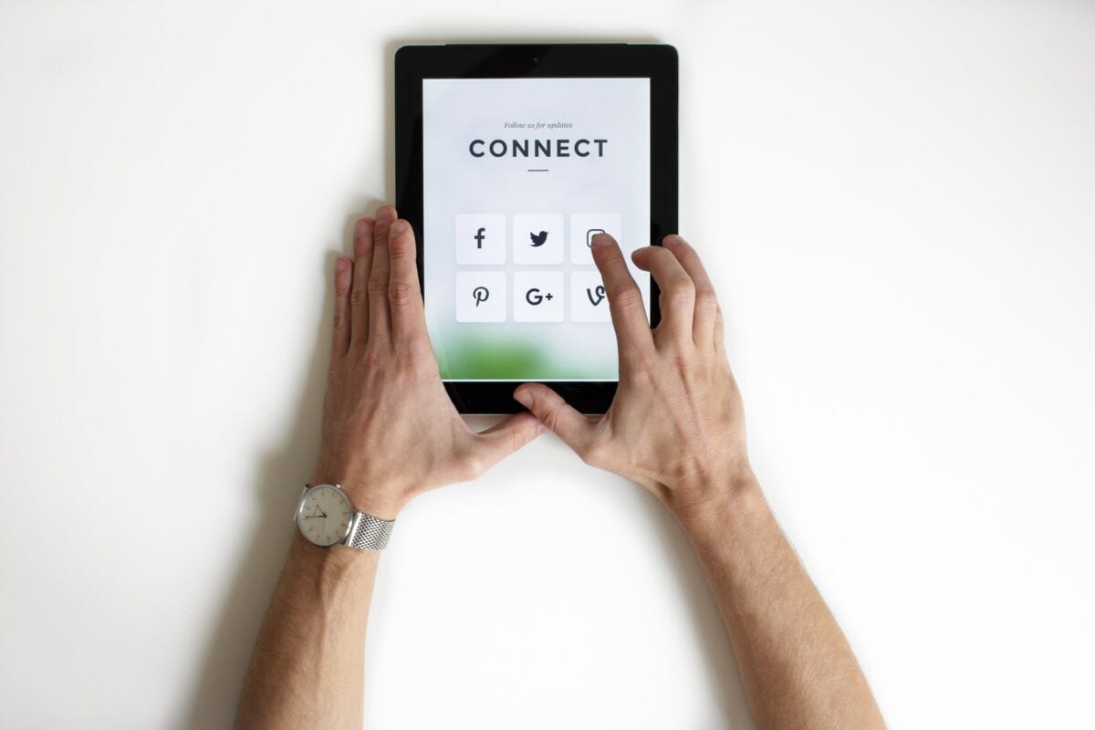 """A person using a tablet that says """"Connect"""" followed by social media icons"""