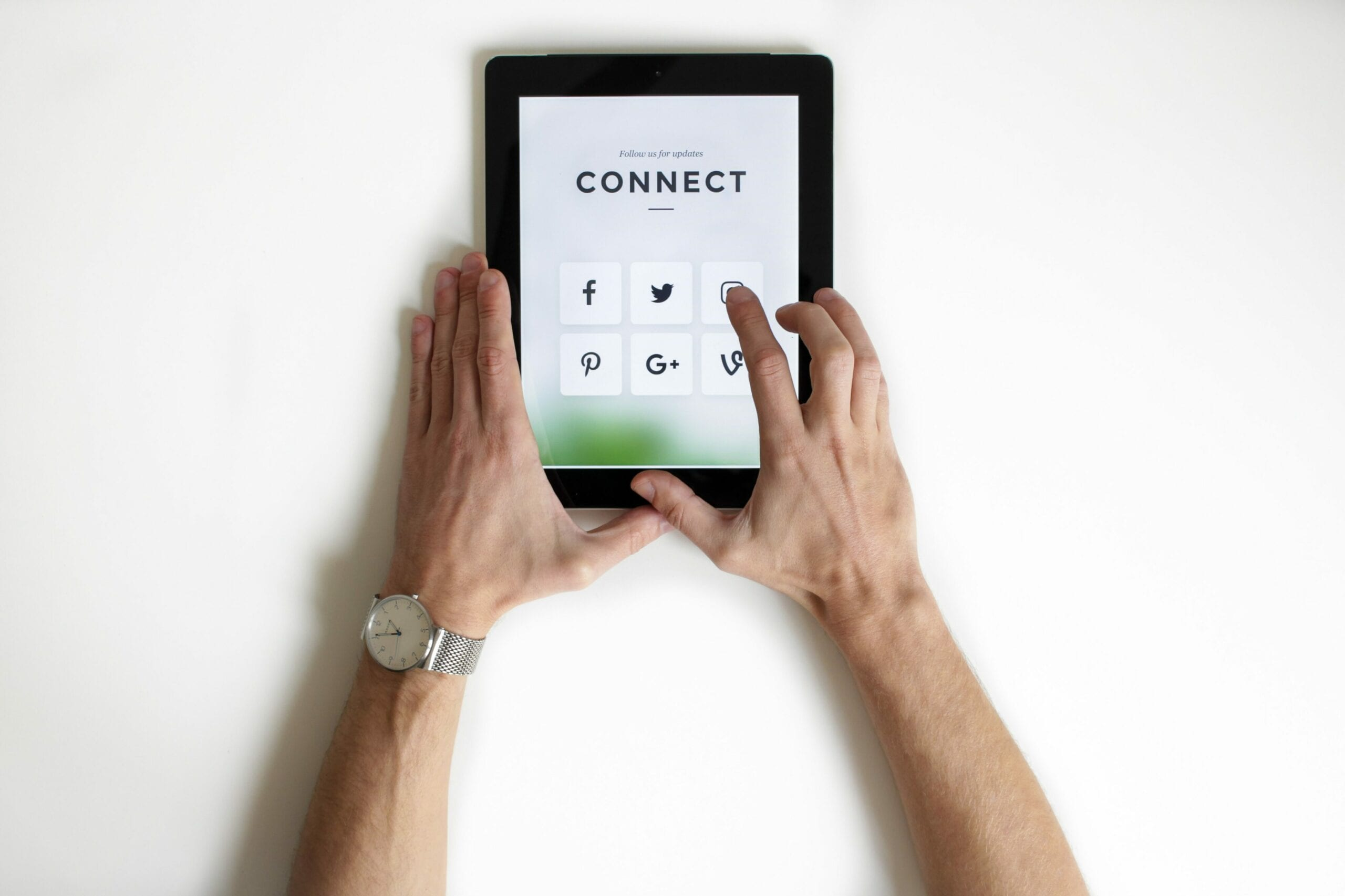 "A person using a tablet that says ""Connect"" followed by social media icons"