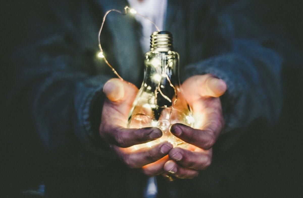 Someone holding a lit lightbulb