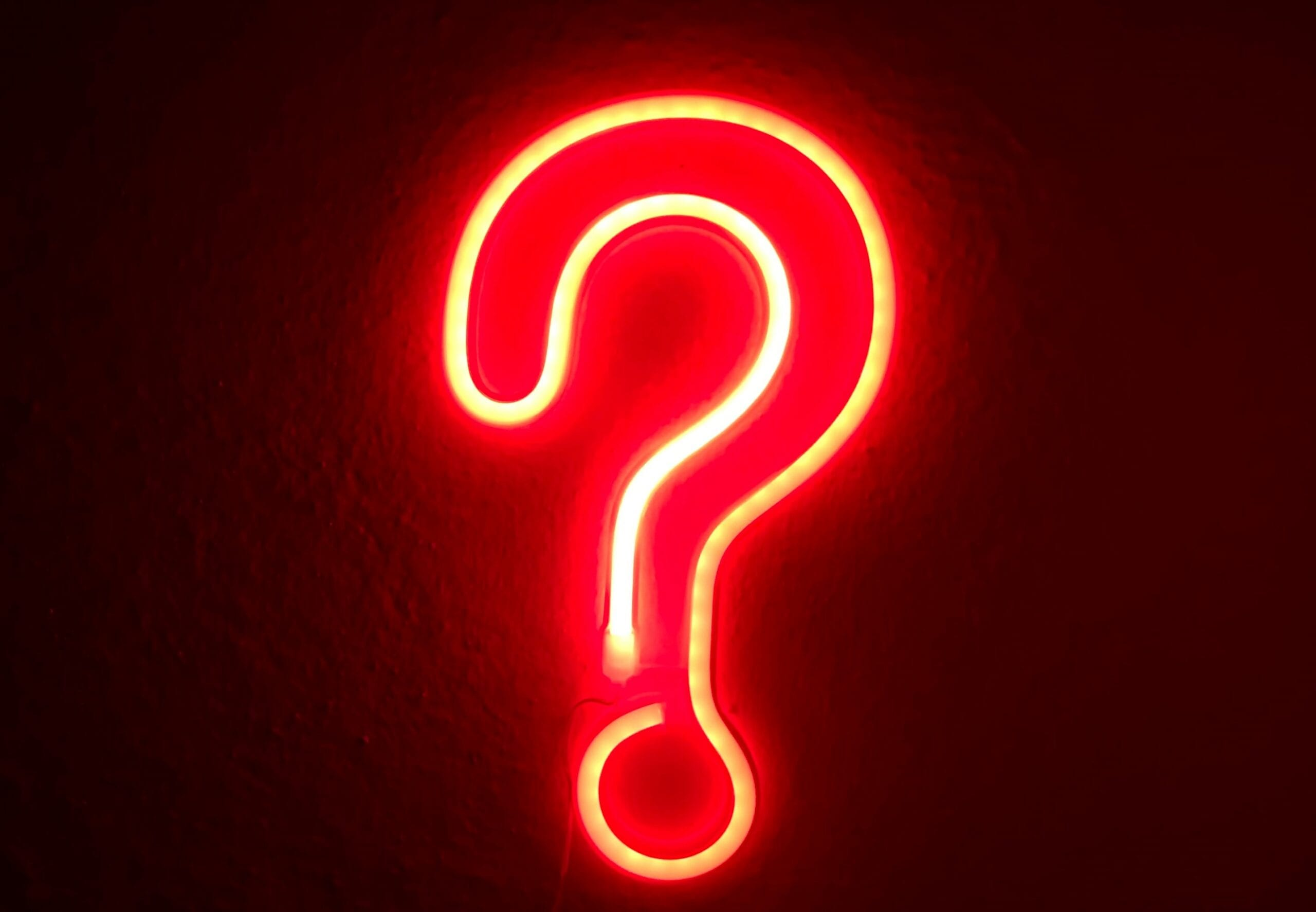 A red, fluorescent question mark