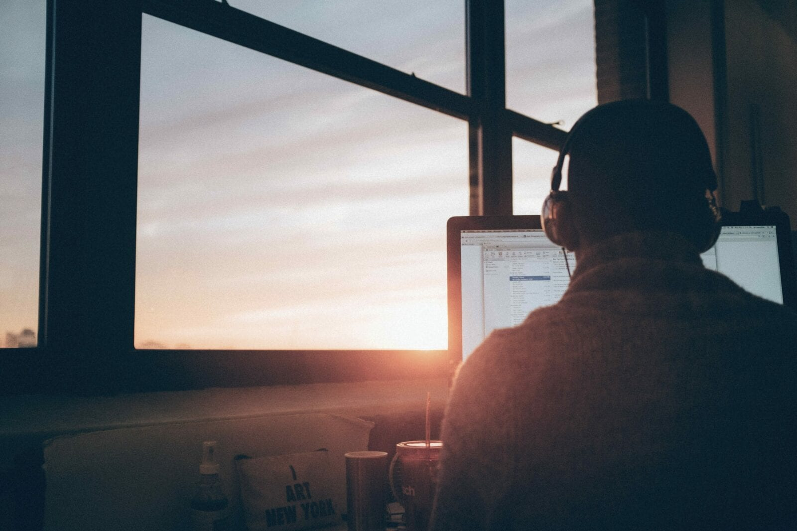 Someone sitting in front of a computer while the sun sets out the window